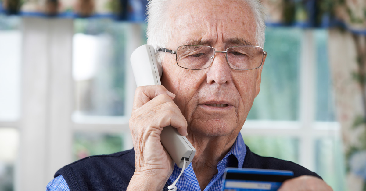 Senior talking on phone with credit card in hand