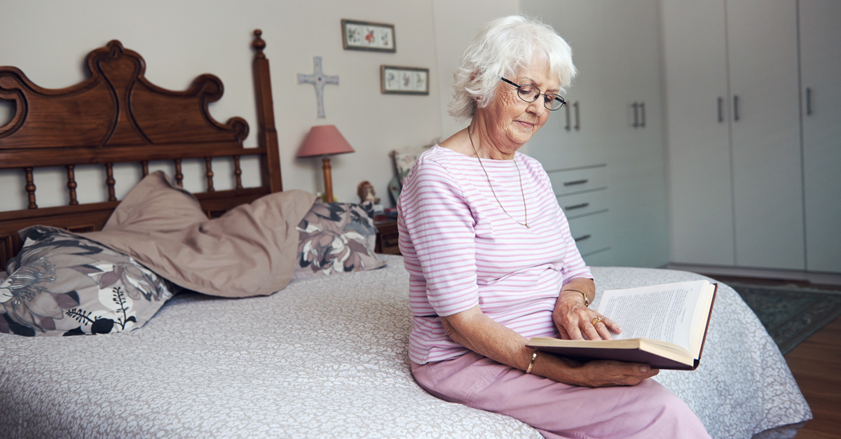 Elderly woman sitting on bed reading